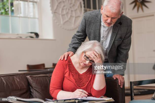 Senior man comforting woman on couch