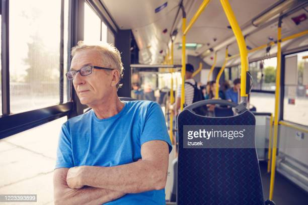 senior man commuting by public transport - izusek stock pictures, royalty-free photos & images