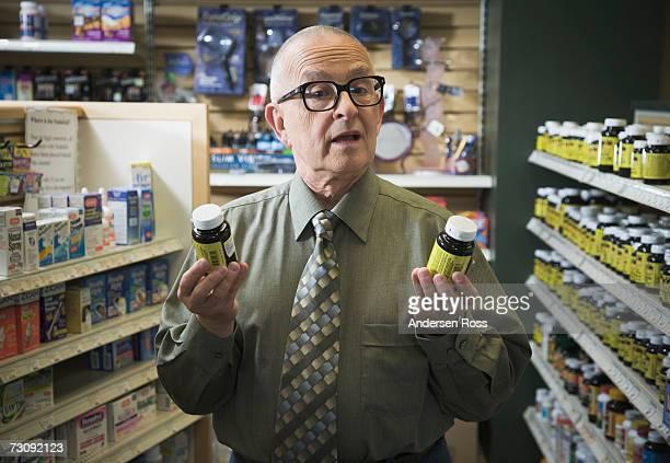 Senior man comparing two pill bottles in pharmacy