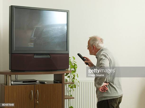 Senior man confused by large television