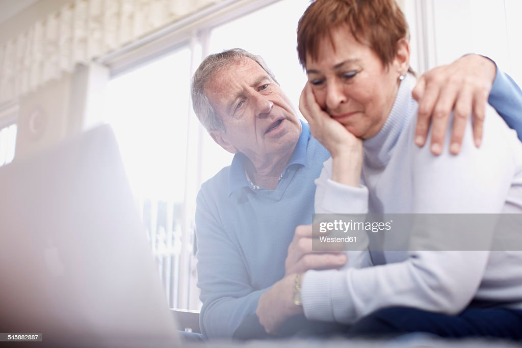 Senior man consoling crying wife at laptop : Stock Photo