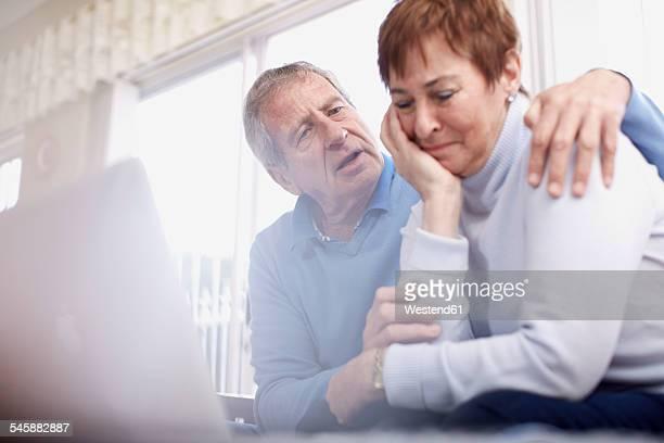 Senior man consoling crying wife at laptop