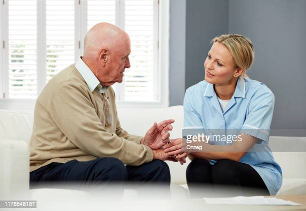 senior man consulting home caregiver - simple living stock pictures, royalty-free photos & images