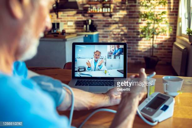 senior man consulting with his doctor online - science and technology stock pictures, royalty-free photos & images