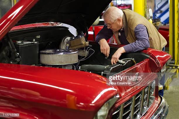 Senior man contemplates auto engine