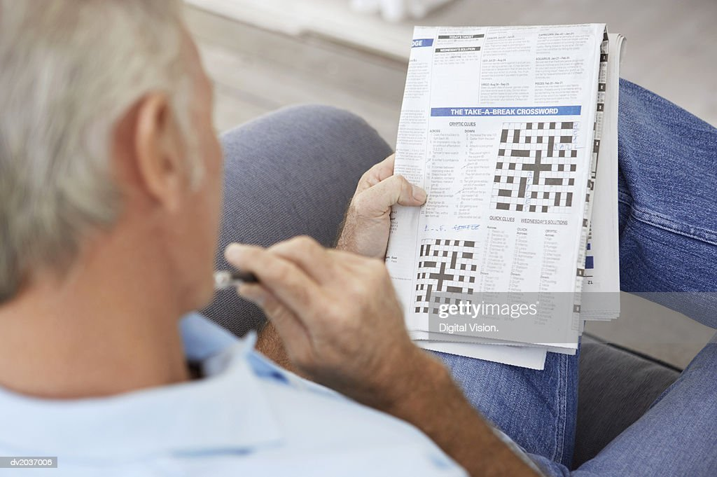 Senior Man Contemplating a Newspaper Crossword : Stock Photo