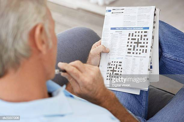 Senior Man Contemplating a Newspaper Crossword