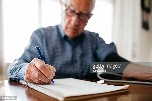 Senior man controlling his blood pressure and writing down the result, close-up