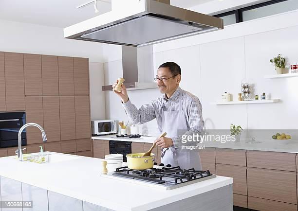 senior man cooking - afzuigapparaat stockfoto's en -beelden