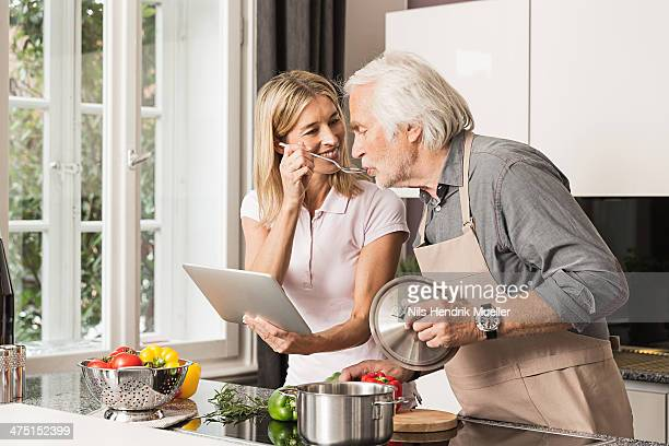 Senior man cooking with daughter, tasting food