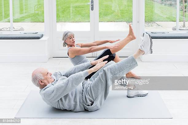 Senior man copying female fitenss instructor stretching legs