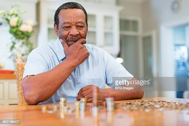 Senior man counting coins, Cape Town, South Africa