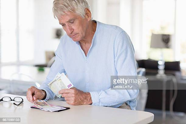 Senior man counting currency note son table