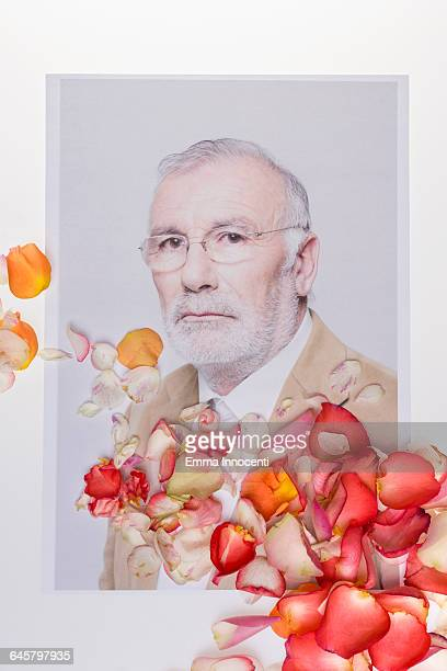 Senior man covered by rose petals