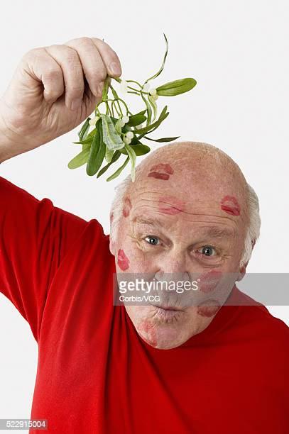Senior man covered in lipstick kisses holding some mistletoe over his head