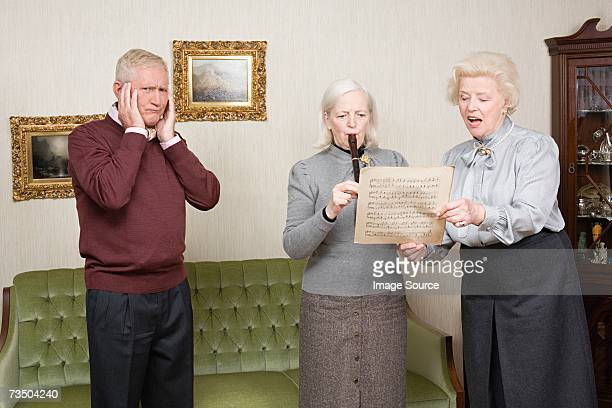 senior man covering ears - recorder musical instrument stock photos and pictures