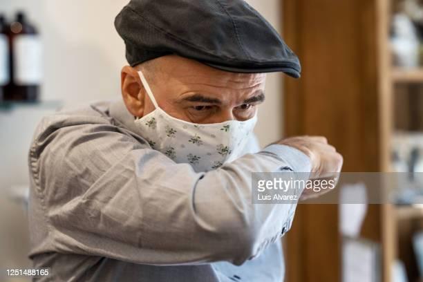 senior man covering mouth with elbow while sneezing - doença infeciosa imagens e fotografias de stock
