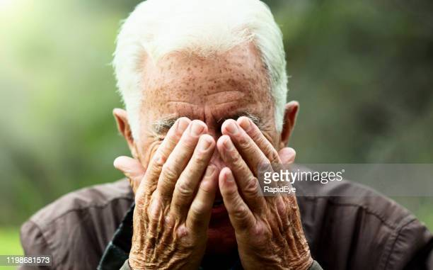 senior man covers his face with his hands, frowning - obscured face stock pictures, royalty-free photos & images