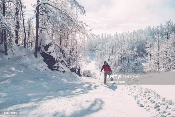 senior man cross-country skiing in european alps - nordic skiing event stock pictures, royalty-free photos & images