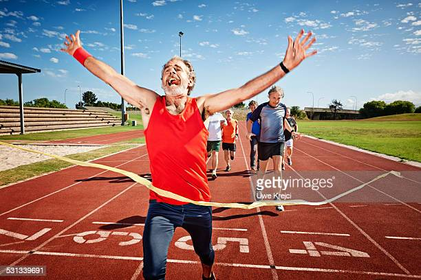 senior man crossing finish line - finishing line stock pictures, royalty-free photos & images