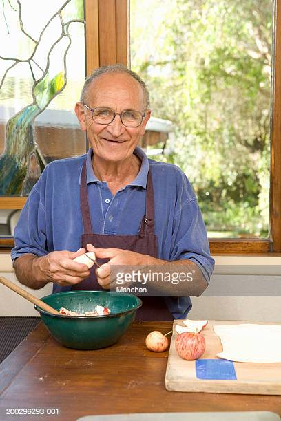 Senior man cutting apples into bowl, smiling, portrait