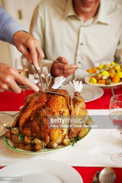 senior man cutting turkey for family at christmas dinner - preparation stock pictures, royalty-free photos & images