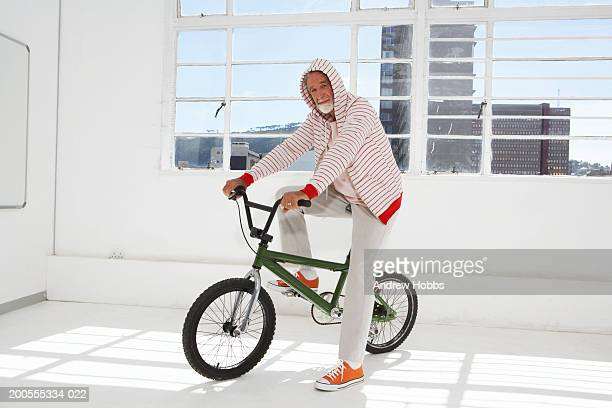Senior man cycling in room