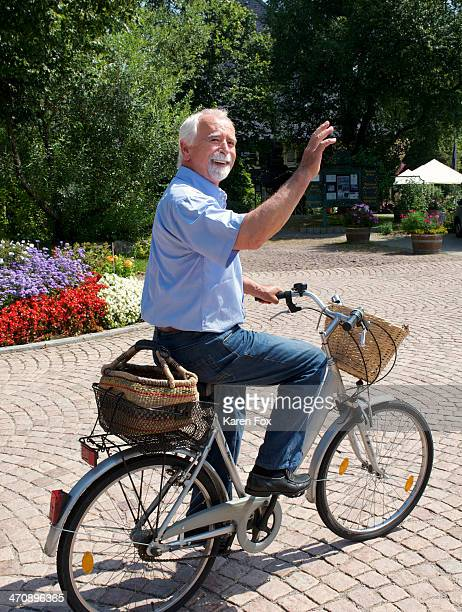 senior man cycling through park - waving gesture stock photos and pictures