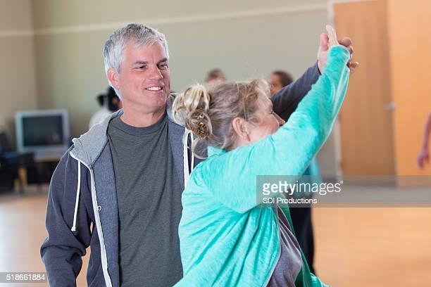 Idoso danças com mulher em altos centro