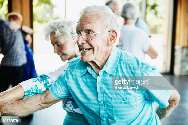Senior man dancing with partner in community center
