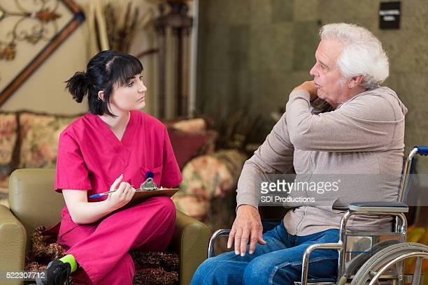 Senior man describes symptoms to nurse