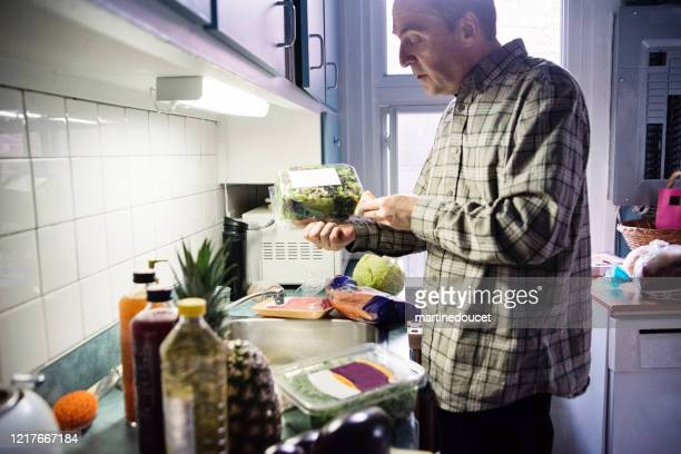 """senior man desinfecting groceries during covid-19. - """"martine doucet"""" or martinedoucet stock pictures, royalty-free photos & images"""