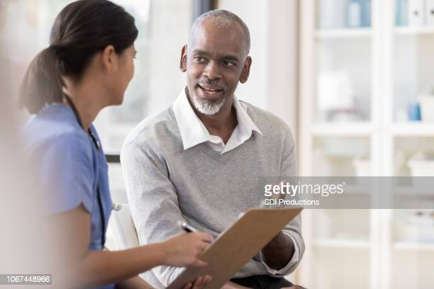 senior man discusses diagnosis with doctor - form filling stock pictures, royalty-free photos & images