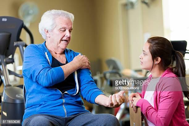 老人男性のセラピストが痛みを緩和し、物理的な説明