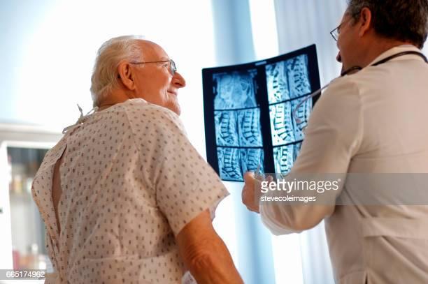 Senior hombre hablar de rayos x con el médico.