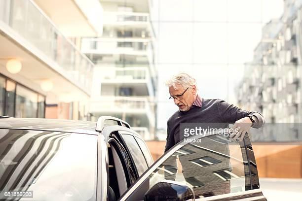 Senior man disembarking from car in city