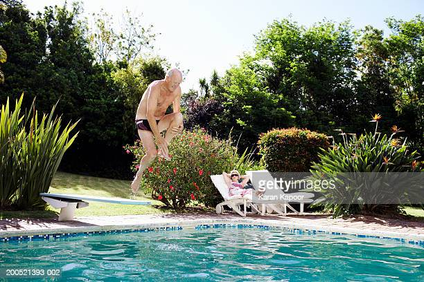 Senior man diving into pool, senior woman sitting on sun lounger