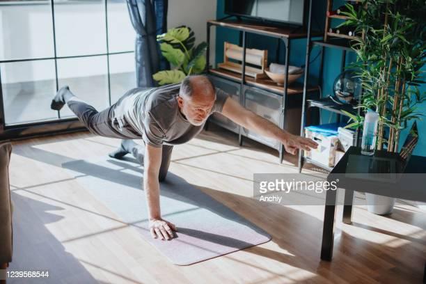 senior man doing balance exercise - sports training stock pictures, royalty-free photos & images