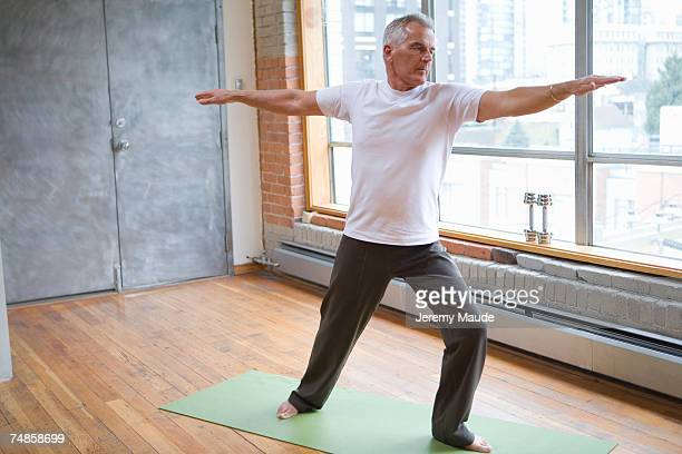 Senior man doing exercise in gym, arms out