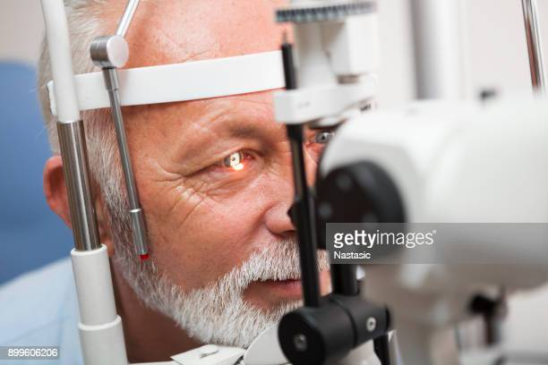 senior man doing eye test with ,close up - eye test equipment stock pictures, royalty-free photos & images