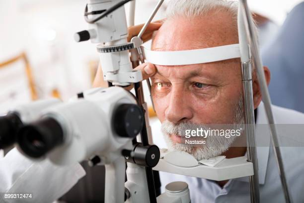 senior man doing eye test with optometrist - optometry stock pictures, royalty-free photos & images