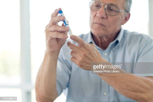 Senior man doing finger prick test