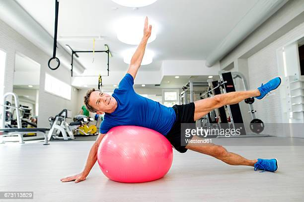 Senior man doing gymnastics on fitness ball in gym