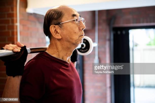 senior man doing muscle training with a barbell - ポジティブなボディイメージ ストックフォトと画像