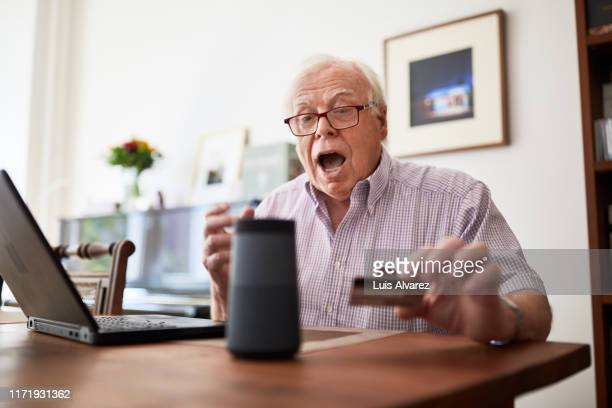 senior man doing online purchase using wireless devices - excitement stock pictures, royalty-free photos & images