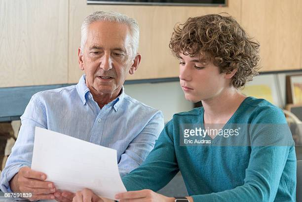 Senior man doing paperwork with grandson in a living room