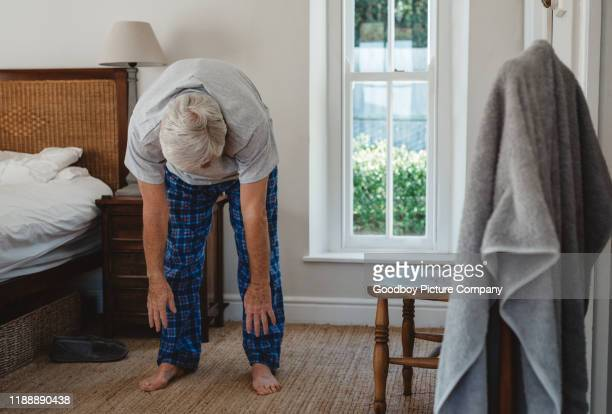 senior man doing stretches after waking up in the morning - bending stock pictures, royalty-free photos & images