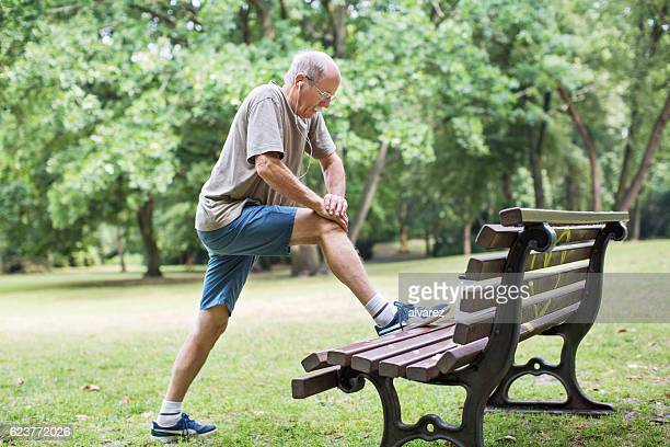 Senior man doing stretching in park