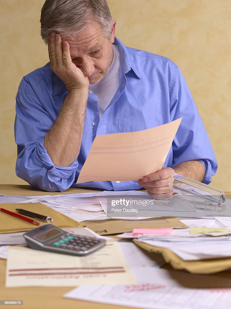 Senior man doing tax return : Stock Photo