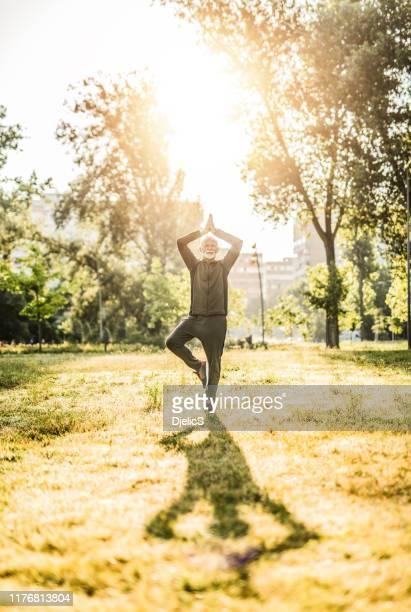 senior mann macht yoga im freien im stadtpark. - einzelner senior stock-fotos und bilder